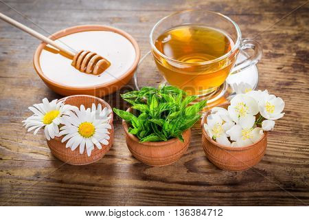 Herbal tea with mint, chamomile, jasmine flowers and honey on old wooden table
