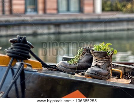 A pair of up-cycled boots on a narrowboat