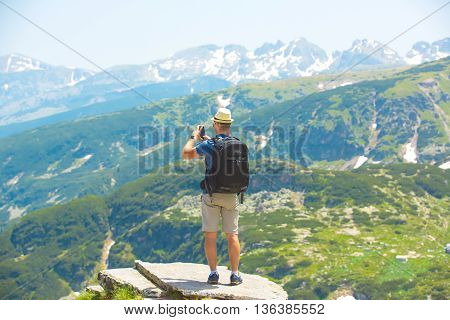 Hiker taking photo of beautiful rila mountains landscape with mobile phone
