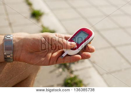 Young man is checking glucose level in his blood.