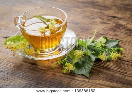 Herbal tea with linden flowers on old wooden table