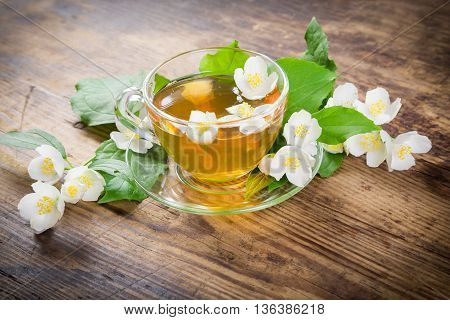 Herbal tea with jasmine flowers on old wooden table