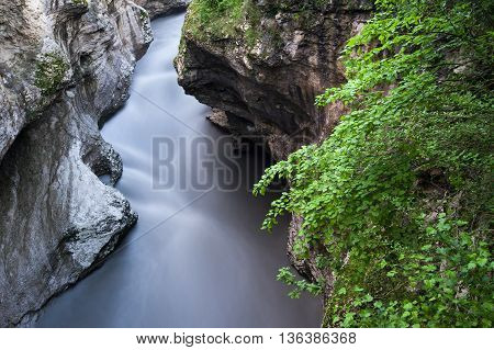 The mountain river in the gorge. Water on the long exposure. Water flow. Green trees in the gorge. Landscape of the river between the rocks. Water flow. Green trees in the gorge.