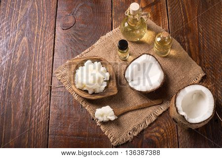 Coconut oil on a rustic table with fresh coconut