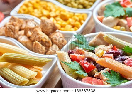 Chicken and vegetable salad in white bowls. Salad ingredients