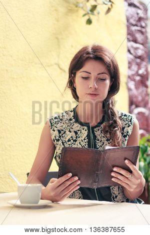 young beautiful woman looks at a restaurant menu