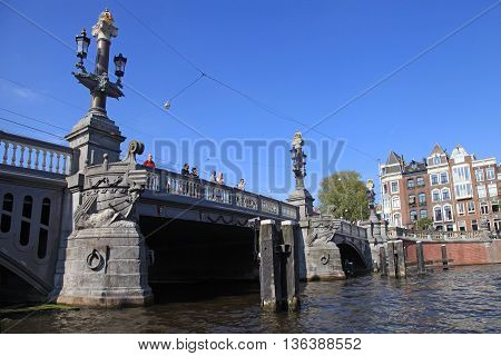 AMSTERDAM, NETHERLANDS - MAY 6, 2016: People on beautiful The Blue Bridge (Blauwbrug) over the Amstel River which connects the Rembrandtplein area with the Waterlooplein, Amsterdam, Netherlands.