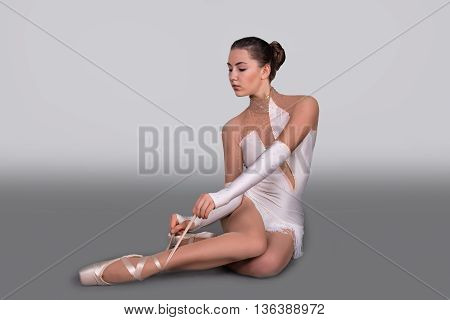 the young ballerina sits and ties pointes