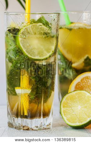 Cold fresh lemonade with ice, lime and lemon close up