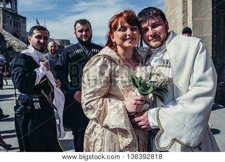 Mtskheta Georgia - April 26 2015. Bride and groom poses for photo after traditional wedding in Svetitskhoveli Cathedral (english - Cathedral of the Living Pillar) in Mtskheta one of the oldest cities of Georgia