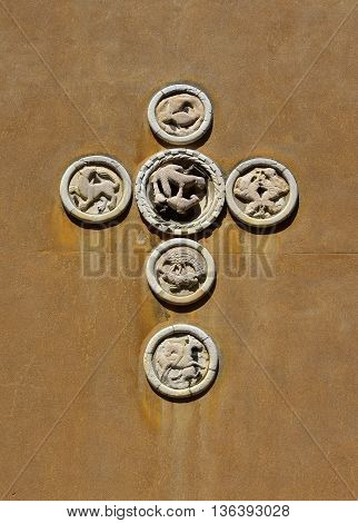 Six medieval patera (venice traditional public art) with animals and bird on a wall to form a cross
