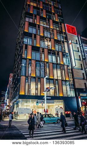 Tokyo Japan - February 27 2015. People passes pedestrian crossing in front of Shiseido Gallery building in Ginza district