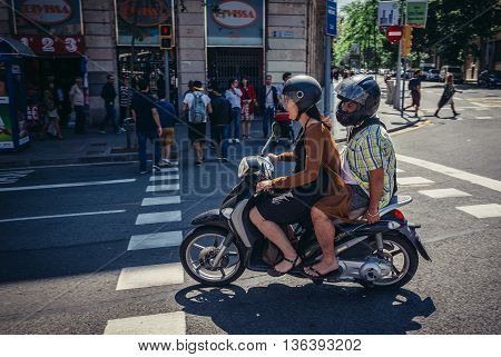 Barcelona Spain - May 23 2015. Woman and man rides motor scooter on street in Barcelona