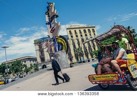 Barcelona Spain - May 24 2015. Tourists rides pedal cab in front of famous sculpture called El Cap (Head) created by Roy Lichtenstein
