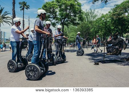 Barcelona Spain - May 24 2015. Segway trip participants looks at street performer in Port Vell district