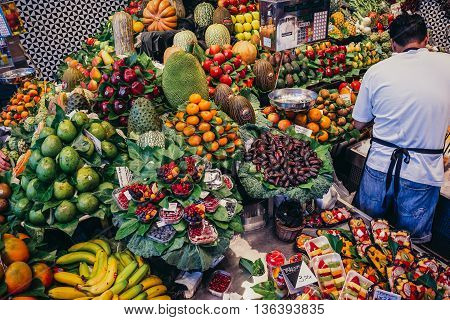 Barcelona Spain - May 26 2015. Man sells fruits and vegetables at public market called La Boqueria foremost tourist landmarks in Barcelona