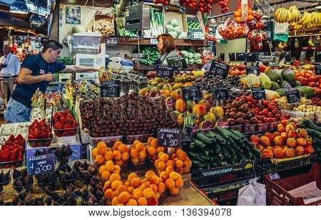 Barcelona Spain - May 26 2015. Woman sells fruits and vegetables at market called La Boqueria foremost tourist landmarks in Barcelona