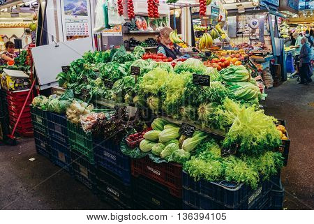 Barcelona Spain - May 28 2015. Woman sells vegetables at market called La Boqueria foremost tourist landmarks in Barcelona