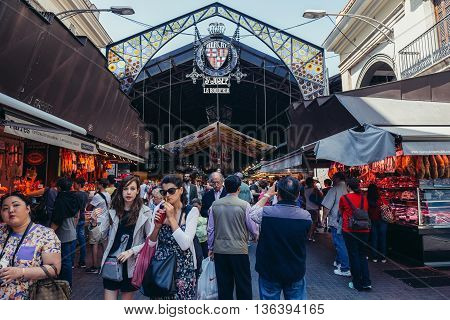 Barcelona Spain - May 28 2015. Tourists and city residents walks in front of main entry of public market called La Boqueria foremost tourist landmarks in Barcelona