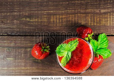 glass of strawberry juice with green leaf on old wooden  background and blurred berries. top view