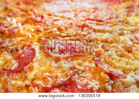 Close up photo of pizza. Macro photo of baked pizza ingredients - cheese with ham and tomatoes. Traditional italian cuisine.