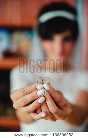Happy bride is holding two wedding rings in her hands