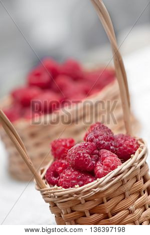 Ripe sweet raspberries in small wicker basket. Close up.