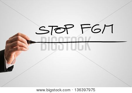 Businessman writing a handwritten sign - Stop FGM - stop female genital mutilation with a black marker pen on a grey background with copy space.