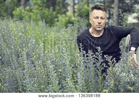 Portrait of handsome mid-adult man posing on summer meadow, image toned.