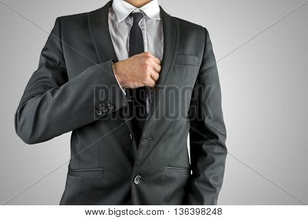 Businessman reaching inside his breast pocket of his suit to retrieve an item such as a business card close up torso view in a suit.