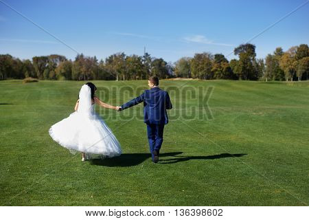 Happy newlyweds dancing on their wedding day in the country on a sunny day