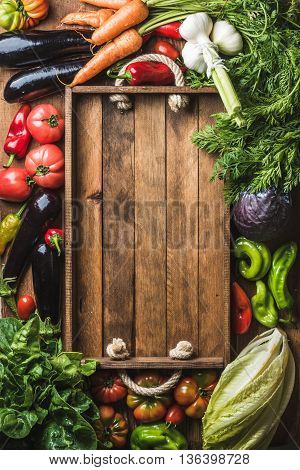 Fresh raw vegetable ingredients for healthy cooking or salad making with rustic wooden tray in center, top view, copy space. Diet or vegetarian food concept, vertical composition