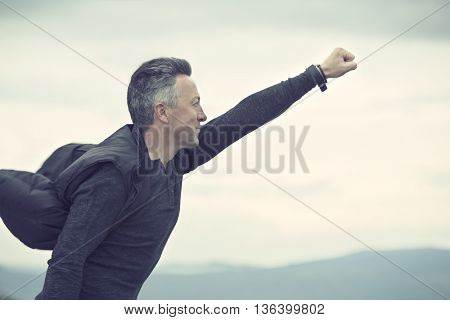 Superhero flying over sky and mountain landscape over sunrise. Success, power,