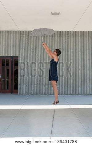 Teen girl with crew cut floating while holding umbrella.