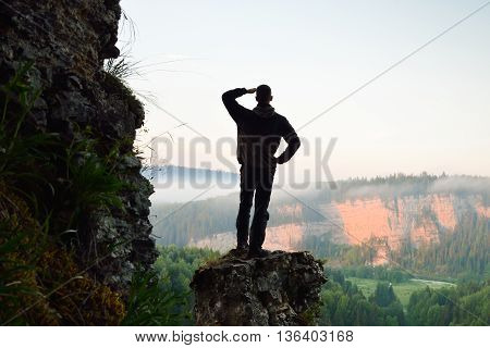 Hiker stands on top of the mountain on sunrise.