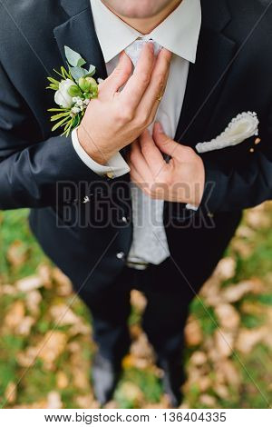 Groom is holding hands on the tie, wedding suit