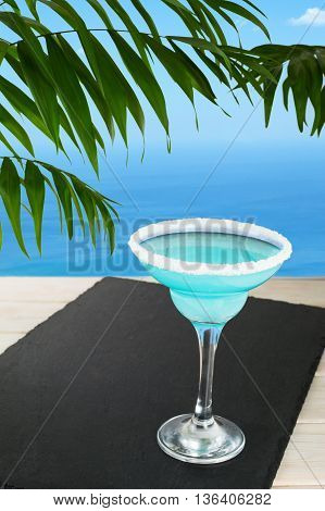 Blue cocktail on the tropical beach. Blue Lagoon margarita martini cocktail. Summer beach alcohol drink. Iced blue cosmopolitan cocktail.