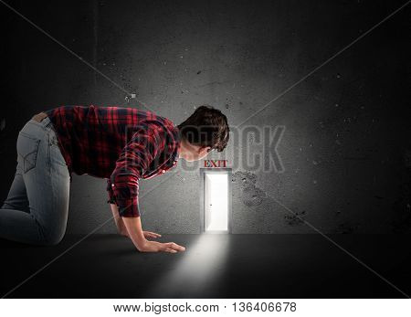 Man looks at a small door on the wall