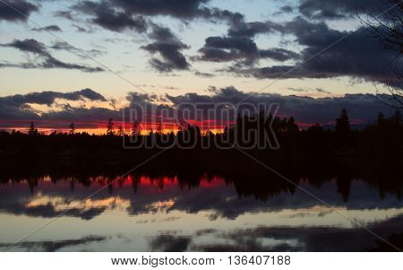 Sunset on a small mountain lake with stunning reflection on the mirror-still water.