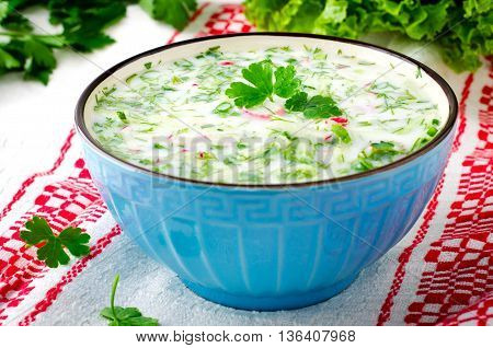 Traditional Slavic cold summer soup okroshka, dietary and vegetarian, in blue bowl