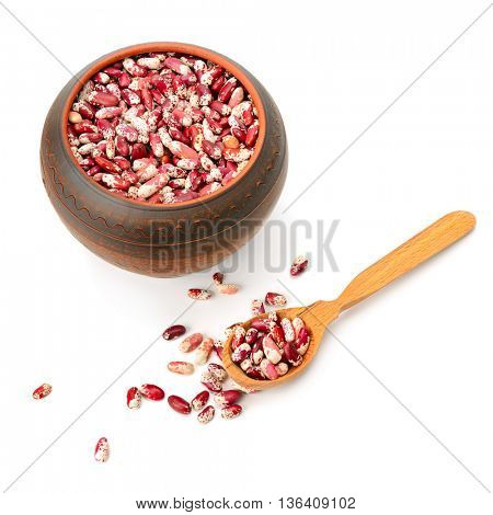 Ceramic pot with beans and a wooden spoon isolated on white background