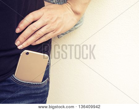 Close up of mobile phone in jeans pocket with poses hand of a person standing against the wall with copy space and artificial light bursts Vintage filter