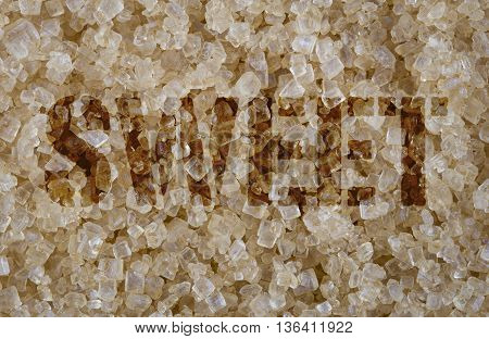 Sweet word screened on background of close focus brown cane sugar