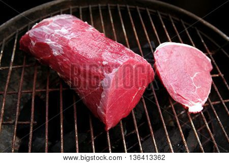 fresh red raw beef fillet steak chunk and slices on black bbq grille ready to cook