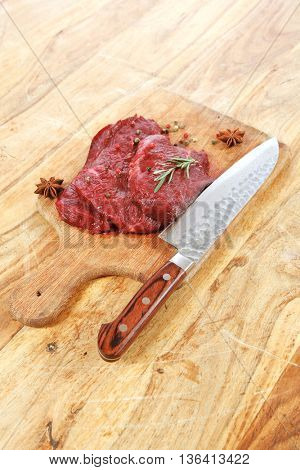 fresh raw beef steak with rosemary twig and sweet hot pea pepper on wood cut plate over table with japanese layered stainless steel knife