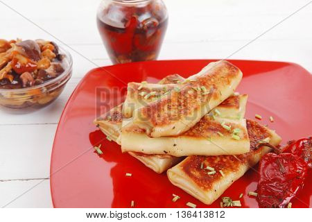 russian food - meat wrapped in a pancake with red hot pepper  and pickled mushrooms served on red plate over wooden table in restaurant