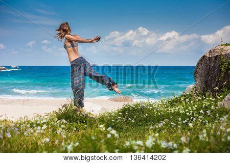 Lady stretching on the sandy beach near blue ocean