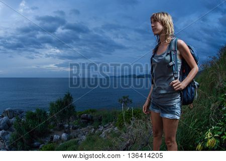 Portrait of a female hiker with backpack and wet clothes on a dark cloudy sky background