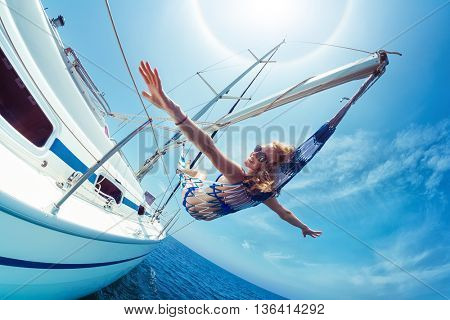 Young lady relaxing in the hammock set on the sail boat while sailing in the open sea