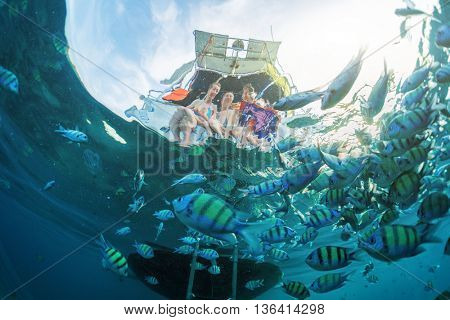 Friends feed fish from a boat, split shot with underwater view